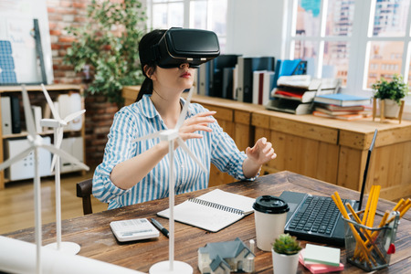 Cutting edge technologies. asian female architect sitting at workdesk in office and testing his new VR headset working on construction green building project. designer with virtual reality goggles 版權商用圖片