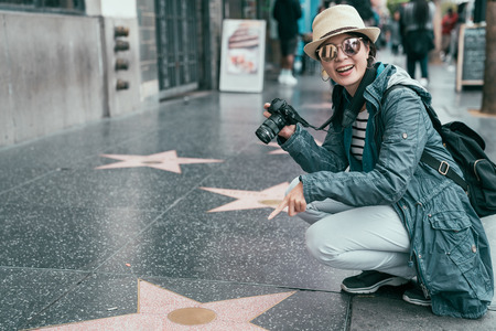 asian female tourist finger pointed star plaques of honored celebrities on Hollywood Boulevard in Los Angeles on sunny day. woman backpacker kneeling down on walk ground showing camera smiling 版權商用圖片