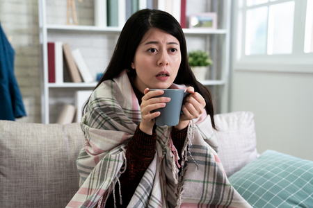 sick young lady in couch sitting with blanket over her shoulders and cup of hot beverage. illness asian woman drinking vitamin c or cocoa to release painful of period coming. female with flu watch tv