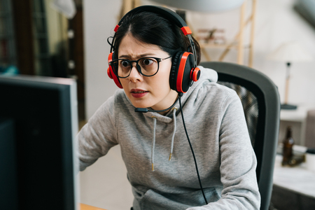 asian female college student with insomnia play video games and ignoring books for studies. girl homebody addicted pc gaming online on summer break. young girl concentrated in glasses and headphones