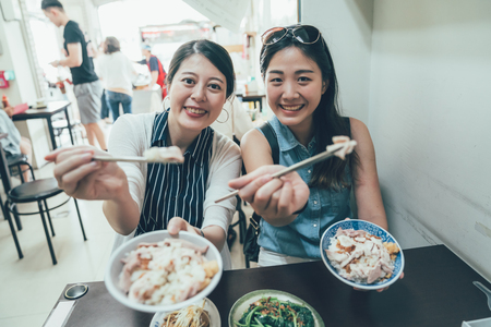 group of best sisters travel in taiwan taipei eating local meal turkey rice sharing to camera holding chopsticks sitting in vendor on summer. smiling attractive young girl friends having lunch.