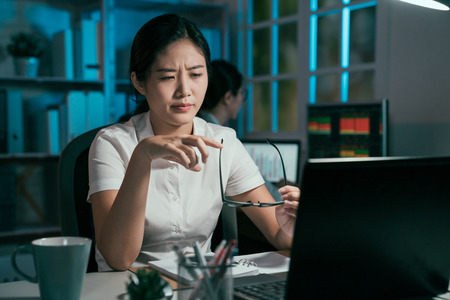 serious asian woman feeling eyes painful hurt overworked taking down glasses relax. young female coworkers hard working on laptop comptuer at late night office together. frowning tired businesswoman Stock Photo