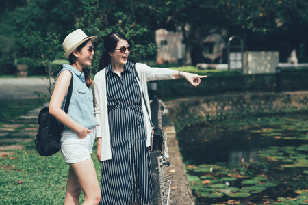 happy asian female tourists travel in japan outdoors. young girl point finger showing sharing pond view of nature lifestyle in park on sunshine day. beautiful ladies in sunglasses standing smiling