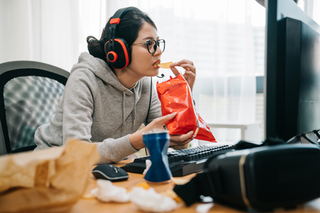 emotional funny college girl enjoying fast food during using computer in headphones. woman having summer break playing online games. young female homebody glasses staring at monitor screen eat chips 写真素材