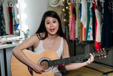 beautiful talent japanese woman singer practicing playing acoustic guitar singing before concert performance in dressing room. young asian musician in white tank top and show not ready in backstage.