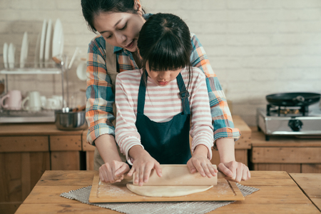 asian mom and daughter using rolling pin together in kitchen kneading dough for happy mothers day homemade cake. woman hugging kid from back teaching baking bread prepared for new year christmas. 版權商用圖片