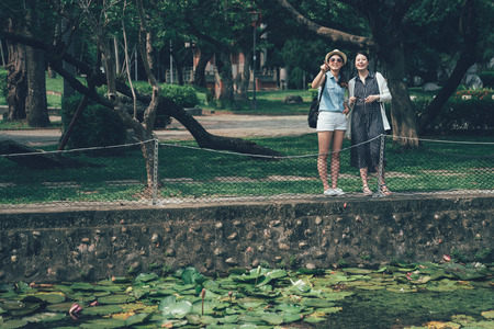 two asian girls standing by pond in park travel in japan kyoto nature outdoor. unready lotus in early summer growing in pool. beautiful female travelers point away showing discussing urban view.