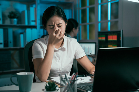two asian female coworkers working at night office. tired businesswoman working on laptop eyes hurt pain massage by hands. colleague manager looking at computer screen sitting in background