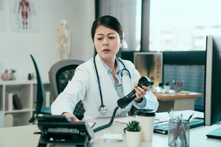 medicine people and healthcare concept. frowning asian female doctor with computer calling on phone at hospital. confused young girl intern nurse having problem using telephone to contact colleague.