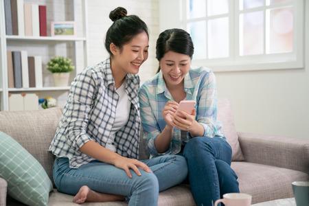 due giovani belle ragazze asiatiche che si siedono sul divano nel soggiorno di casa. amiche che usano lo smartphone guardando video divertenti del programma ricreativo online. donna coreana nel divano a fare shopping su internet