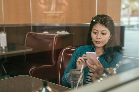 beautiful young asian woman tourist chatting on mobile phone sitting in diner restaurant in los angeles usa. elegant female local in sunglasses american lifestyle having lunch eating using smartphone