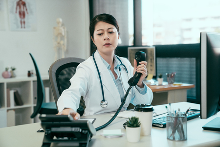 Doctor consulting with nurse about patient situation over phone. young asian woman medical staff sitting at desk in clinic office pick up telephone call communicate having conversation with coworker.