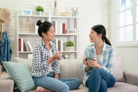 two happy young asian female friends with coffee cups conversing in living room at home. group of beautiful girls bestie sitting on couch relax in bright cozy apartment enjoy tea in weekends gossip Stockfoto