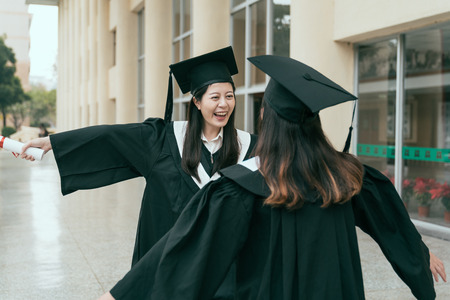 Happy graduated young multi ethnic students hugging. beautiful smart university learner finished college sending care love emotion to friend classmate smiling laughing open arms hands out building