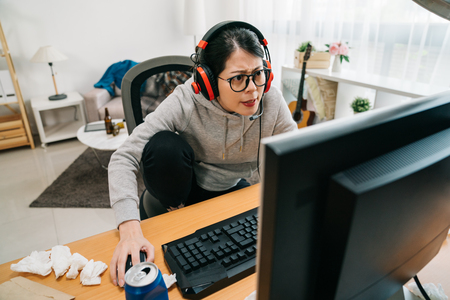 Gamer play first person shooter on high end pc. young asian woman playing shooting video game inside messy room on table used tissue paper beverage can. girl homebody on summer vacation lifestyle Stock Photo