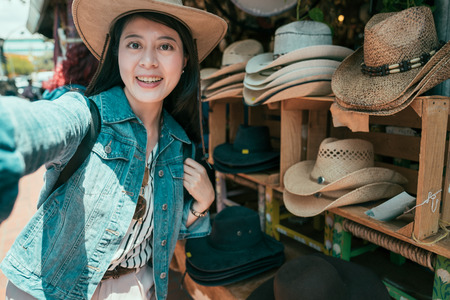 Beautiful asian woman taking selfie buying hats at olvera street vendor. Consumerism shopping traveling lifestyle concept. young girl tourist make self photo wearing straw hat in local mexico market