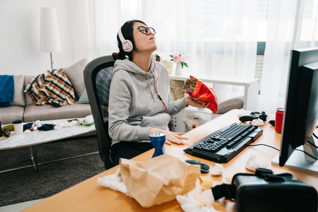 lazy college girl in messy dirty bedroom with order in junk food snack enjoy unhealthy life on summer break. happy young asian weird woman with headphones and glasses laughing binge watching online