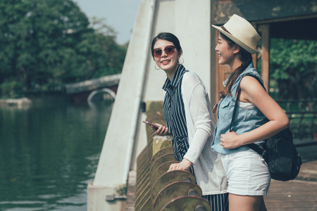 two young girls asian travelers leaning on railing in japanese traditional building wood house outdoor standing in balcony by pool. women tourists enjoy sunshine pond view in park smiling look camera Stock Photo