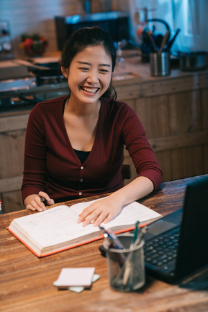 Happy asian female student learning online and taking notes in notepad doing homework looking at laptop screen on desk at home kitchen. young college girl stay up late hardworking using notebook pc.