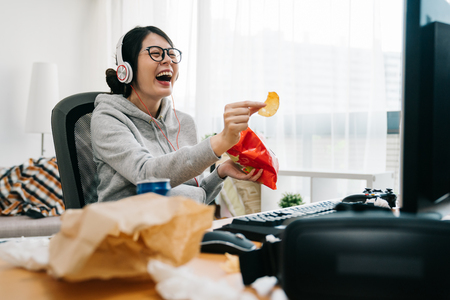happy asian female nerd holding bag of chip snack junk food with trash on desk looking monitor laughing. relax lazy teenage girl at home watch comedy movie on computer with headset sit in messy room Stockfoto
