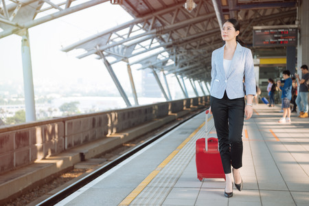 Full length portrait of traveling business woman walking with bag suitcase in train station platform. young asian office lady worker commute to airport for trip to visit customer abroad with luggage