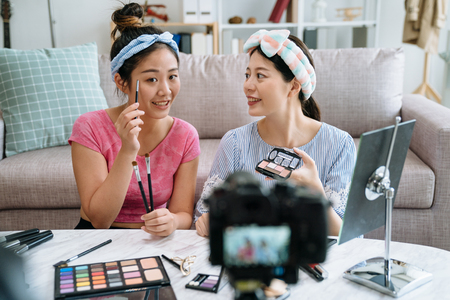 two asian women beauty blogger recording video tutorial showing how to apply make up. Female vloggers recording makeup vlog for online channel by professional camera sitting on floor in living room 版權商用圖片