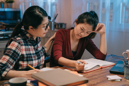 smart woman friend in glasses comforting to sad student with failed exam sitting in night home kitchen prepared for test again. two young girls studying in late midnight. lady consoling crying sister Stock Photo