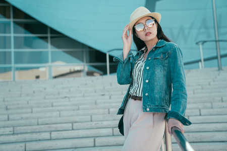 Relaxed young asian woman traveler in hat and sunglasses leaning on city stairs railing.