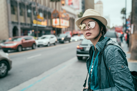 Young beautiful asian woman tourist in sunglasses and hat outdoor in city waiting for cab hailing taxi. travel transport commuter concept. Stock Photo