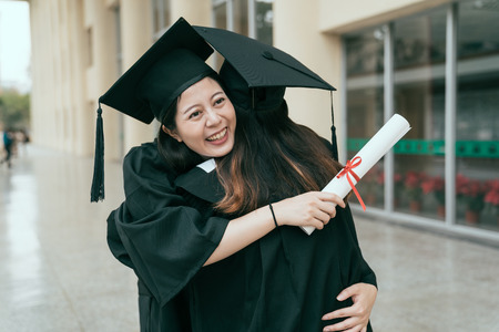 Pair of multi asian girl students hugging on graduation day at university building hall having fun and saying good bye. Education qualification gown diploma concept. friendship genuine lifestyle