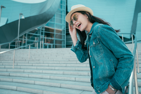 young girl tourist happy smiling with sunglasses and hat standing outdoor of  building Stock Photo