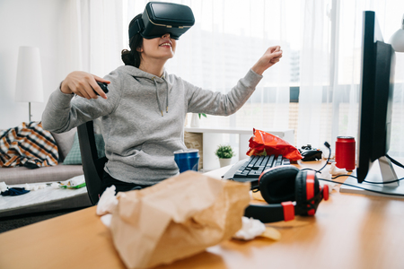 Cheerful young female college student exploring virtual reality glasses sitting in messy dirty room at table of trash garbage used tissue. happy smiling girl geek in vr goggles having fun in summer