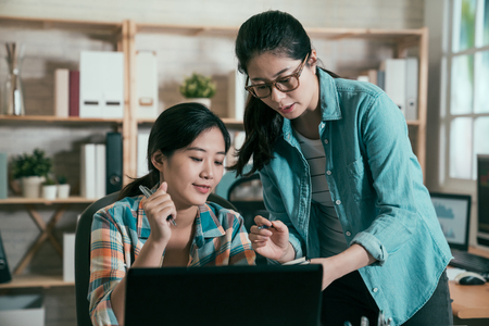 Working together on project. Two confident young asian women looking at laptop monitor and notebook discussing new plan of cooperate in studio office. elegant girls in modern workplace talking. Imagens