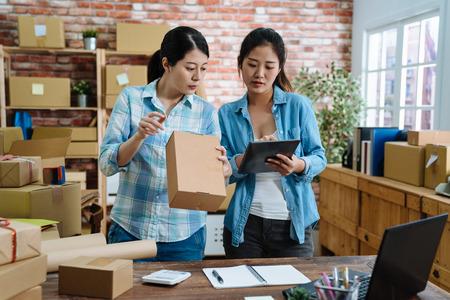Socios de trabajo en equipo de mujeres jóvenes que empaquetan el pedido en una caja usando el panel táctil para hacer la entrega al cliente. Dos colegas asiáticas con tableta comprobando el número de mercancías y cartones preparados en la oficina. Foto de archivo