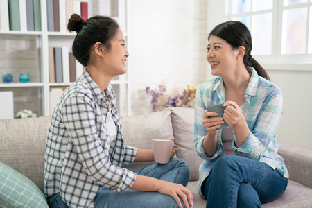 Happy asian sisters rest on sofa in living room talking planning future life holds cups drinking tea. two young girls best friends in shirt and jeans chatting laughing with hot coffee cup in hands. Banque d'images - 123194262