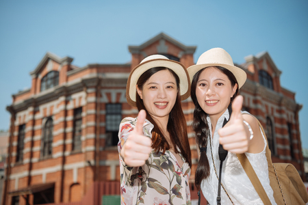 two asian korean young female tourists face camera with thumb up hand sign in front of a building. Фото со стока - 123260115
