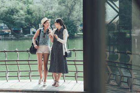 Young joyful girls friends leaning on railing of wooden gazebo standing by pond in park with different trees. two asian women travelers looking on smart phone screen laughing having fun relax outdoor 스톡 콘텐츠