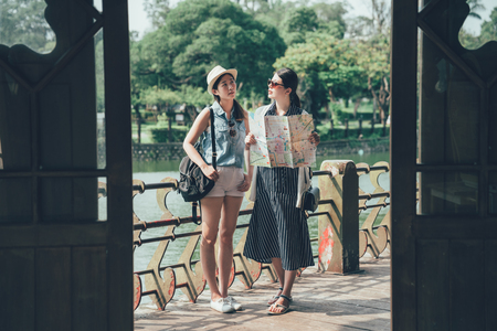 two asian women tourists with paper map standing outside wood japanese style temple searching right way information. beautiful ladies backpacker in entrance of pavilion by pond in park. travel japan Stock Photo