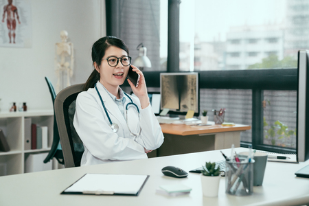 Laughing asian doctor woman listening to patient at mobile phone at hospital. young girl intern nurse wear white coat sitting in clinic office smiling talking on cellphone relax having break time. Stock fotó