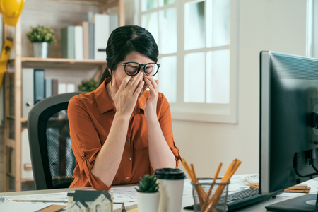 Feeling tired. Frustrated young asian woman architect looking exhausted and covering face with hands while sitting at working place in architecture company. girl engineer rubbing hurt eyes in office Imagens