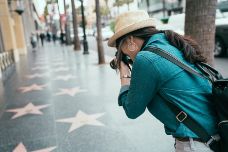 back view of asian female photographer taking photos of star sign on street in Hollywood Boulevard by professional lens camera. 写真素材