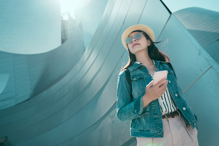 Stylish asian girl backpacker with smile holding mobile phone in hand outdoor with concert hall building. young woman tourist in sunglasses and straw hat enjoy sunlight in city.