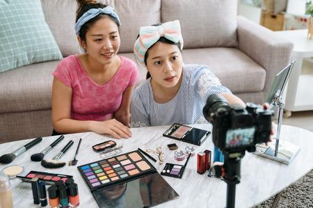 deux blogueuses beauté prêtes à enregistrer une vidéo de tutoriel de maquillage avec des produits cosmétiques sur une table dans le salon.