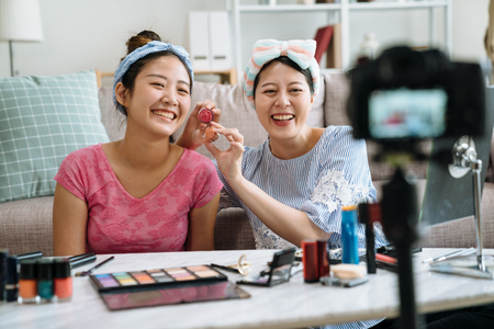 Two beauty blogger cute girls presenting beauty cosmetic products and broadcasting live video to social network.