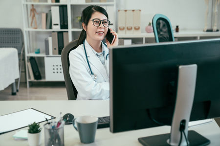 medicine people and healthcare concept. happy female doctor in glasses talking on cellphone at hospital. young woman medical worker in clinic office listening to patient on smart phone joy smiling Stock fotó