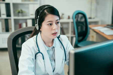 asian woman doctor in telemedicine concept. young female medical nurse sitting in hospital wearing headset pick up online phone call and answering solve patient problem. clinic worker work computer Stock Photo