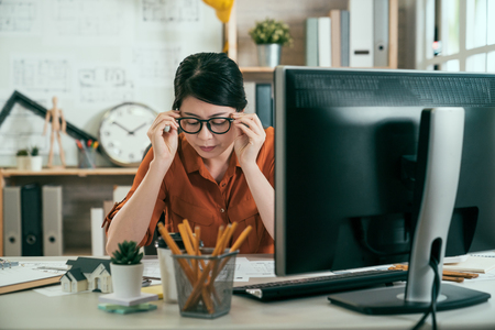 Young asian woman architect taking off his glasses at office. female construction engineer finishing draw project on blueprints. lady designer putting elbows on desk with papers at desktop computer.