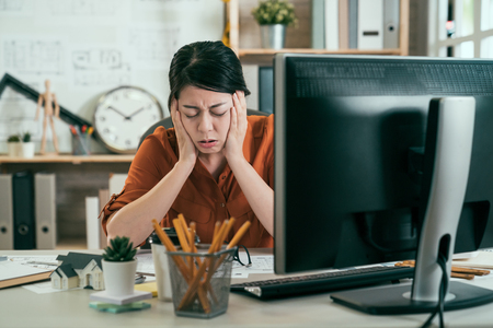 asian woman architect engineer covering ears ignoring annoying loud noise plugs ears to avoid hearing sound. Noisy music problem. frowning upset female designer sick tired hand on face Stock Photo