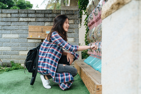 young asian chinese girl traveler kneeling down on grass lawn outdoor playing japanese capsule toy machine in japan. beautiful teenager female with backpack having fun in farmer market insert coin Banque d'images