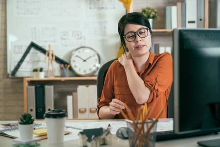 Young female asian architect in shirt feels neck pain massaging tensed muscles after sedentary work sitting in office. woman employee having computer syndrome suffers from chronic cervicalgia ache